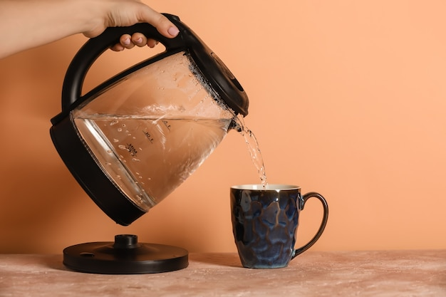 Woman pouring hot boiled water from electric kettle into cup on table