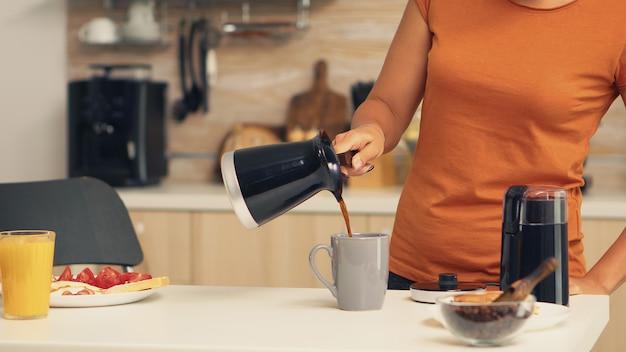 鍋から朝カップにホットコーヒーを注ぐ女性。自宅で主婦が朝食のためにキッチンで挽きたてのコーヒーを作り、飲んで、仕事に行く前にコーヒーのエスプレッソを挽く