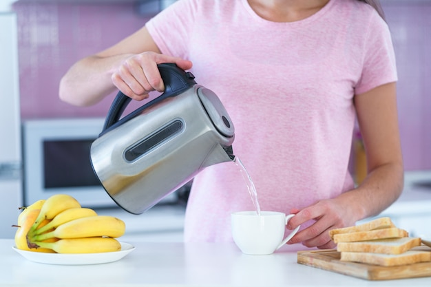 Woman pouring hot water from electric kettle for brewing tea for tea break in the kitchen at home