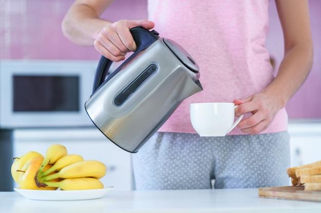 自宅のキッチンでお茶の時間のお茶を醸造するための電気ポットからお湯を注ぐ女性
