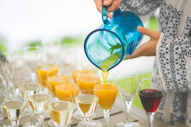 Woman pouring juice into the glasses