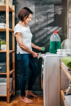 Woman pouring liquid laundry detergent into washing machine
