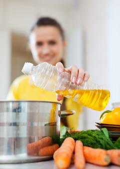 Женщина наливает масло из бутылки в кастрюлю