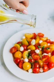 Женщина наливает оливковое масло в свежий здоровый салат с помидорами черри и моцареллой.