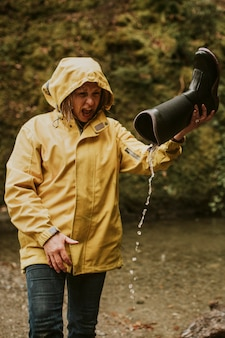 Woman pouring out water out of wellington boot in the forest