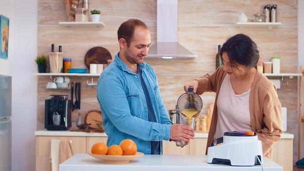 Женщина наливает вкусный смузи из блендера в очки для нее и мужа. веселая семья делает вместе органические здоровые свежие питательные вкусные соки на завтрак из свежих фруктов во время диеты.