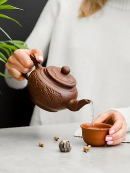 粘土のティーポットからお茶を注ぐ女性