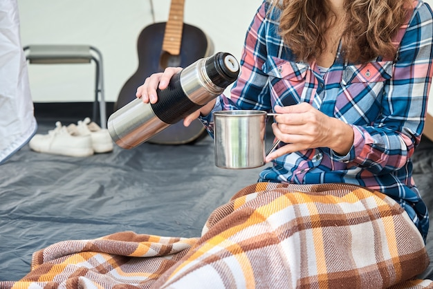 Woman pouring tea from thermos in camping tent