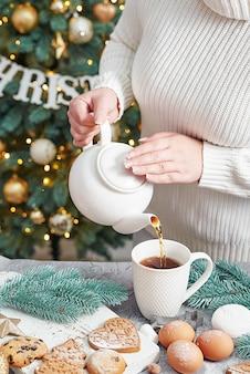 カップにお茶を注ぐ女性