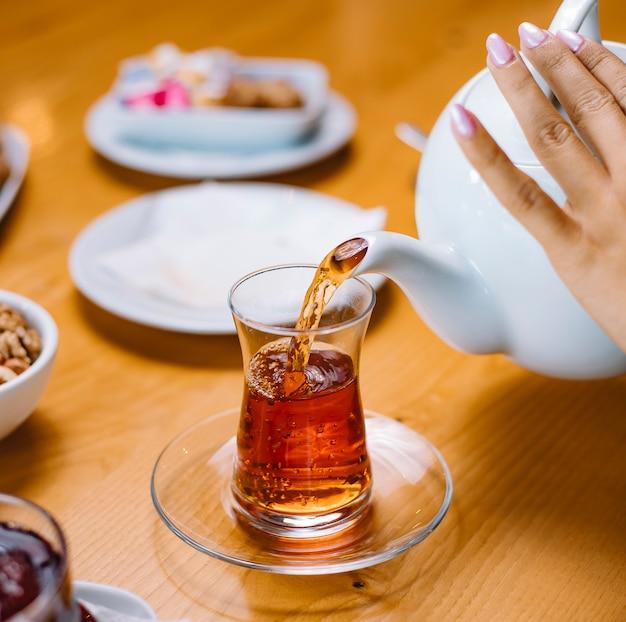Женщина наливает чай в стеклянный вид сбоку