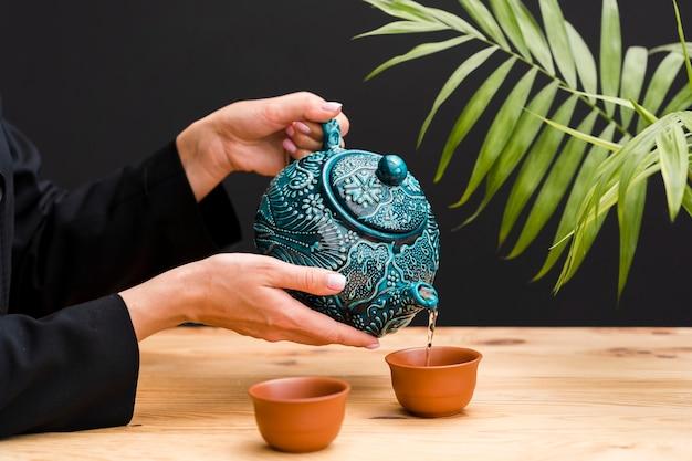 ティーポットと粘土のカップでお茶を注ぐ女性