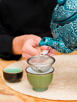 Woman pouring tea in teacup using strainer