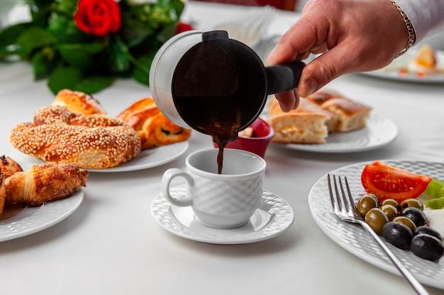 Женщина наливая турецкий кофе в взгляд со стороны кофейной чашки