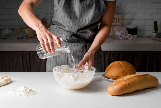 Woman pouring water over dough