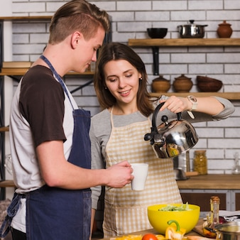Woman pouring water from kettle into mug for man