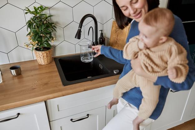 Woman pouring water to glass cup from kitchen sink. young european mother holding her newborn baby. interior of kitchen in flat apartment. concept of motherhood and child care