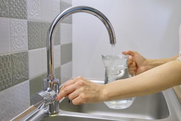 台所の蛇口から水差しに水を注ぐ女性、クロムミキサーの手のクローズアップ