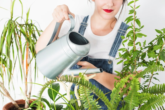 Woman pouring water on plants with watering can