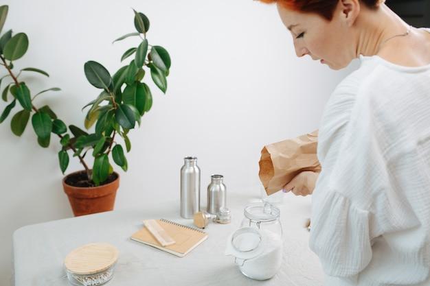 Женщина наливает белый порошок в банку из бумажного пакета. экологически чистые предметы на столе.