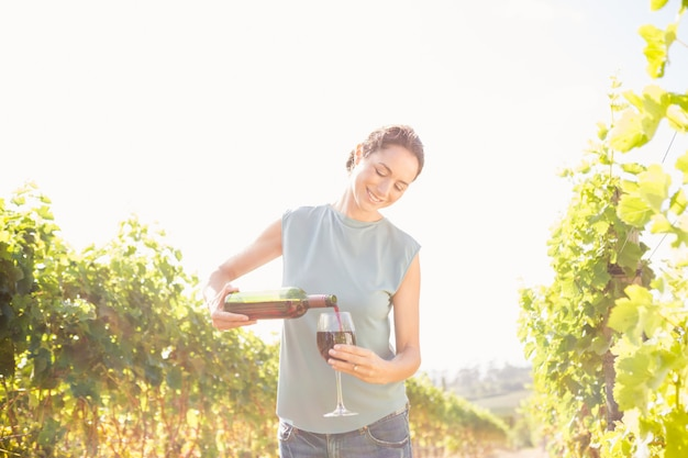 Woman pouring wine from bottle in glass on sunny day