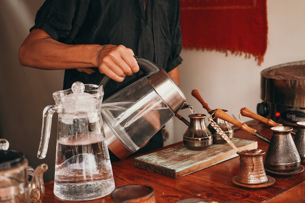 A woman pours boiling water into a cup. the barista prepares coffee on the sand. traditional coffee preparation.