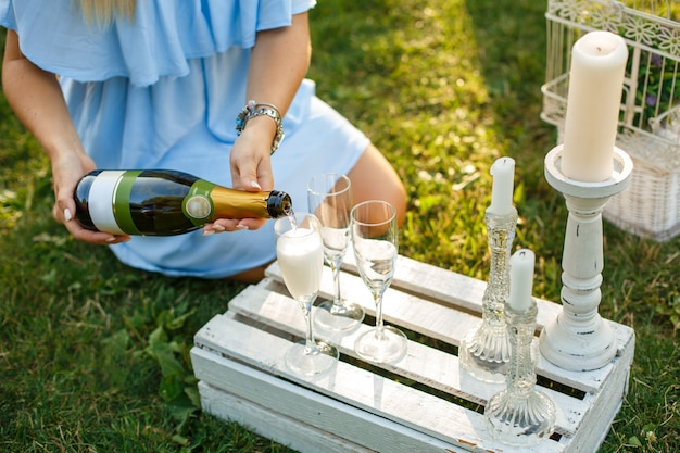 Woman pours champagne from bottle to glass on sunny green park