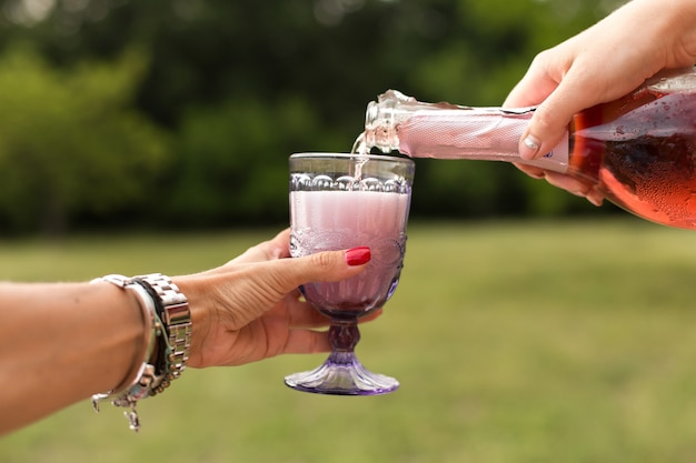Woman pours champagne in glasses at picnic pary.