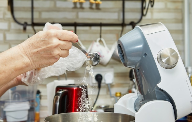 Woman pours flour into the mixer bowl to make sun-dried tomato muffins.