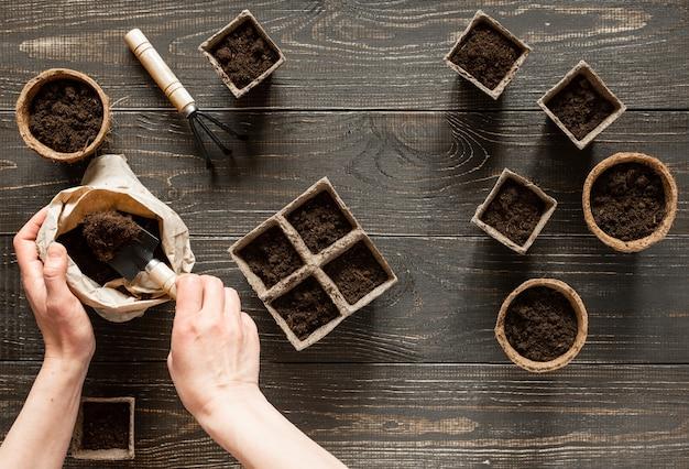 여자는 환경 친화적 인 냄비에 땅을 부어 묘목, 나무 배경에 냄비, 땅과 정원 흙손과 갈퀴가있는 작은 가방을 심습니다.