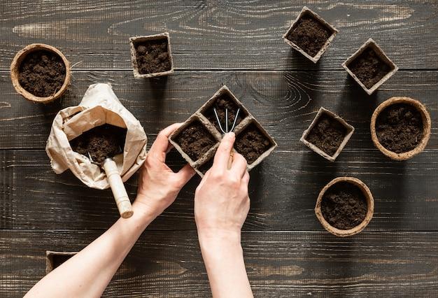 여자는 묘목을 심기 위해 친환경 냄비에 땅을 붓고, 나무 배경에 냄비, 땅과 정원 흙손과 갈퀴가 있는 작은 가방