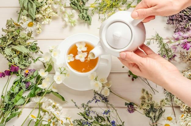 Женщина наливает травяной чай с жасмином на белый деревянный.