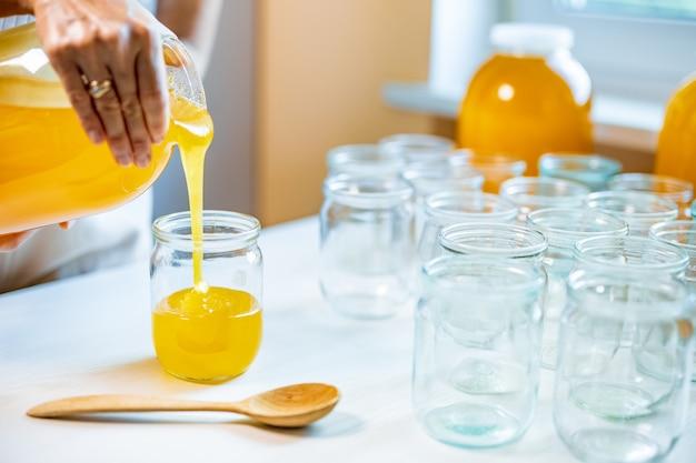 女性は白いテーブルの上の透明な瓶に蜂蜜を注ぐ