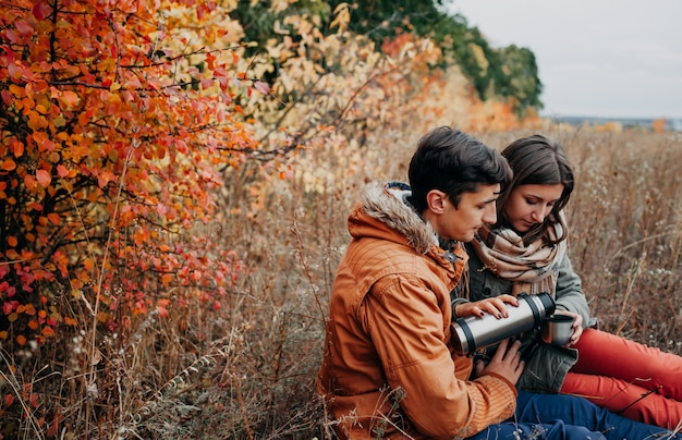 Woman pours hot tea out of thermos in autumn forest. couple in love having drinks