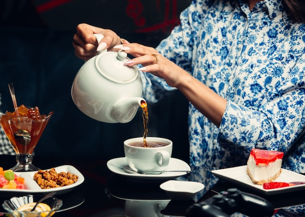 Женщина наливает чай из чайника в белую чашку, чизкейк, варенье