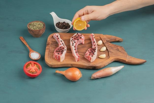 여자는 파란색 테이블에 요리하지 않은 고기 조각에 레몬 주스를 따른다.