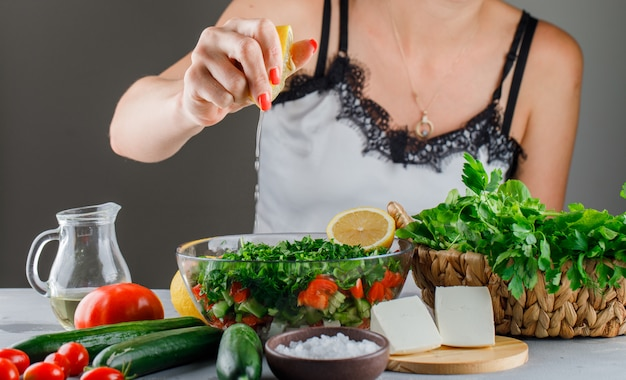 Woman pours lemon juice on salad in a glass bowl with tomatoes, cheese, greens, cucumber side view on a gray surface