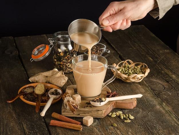 Женщина наливает чай масала со специями, согревающий напиток из индии
