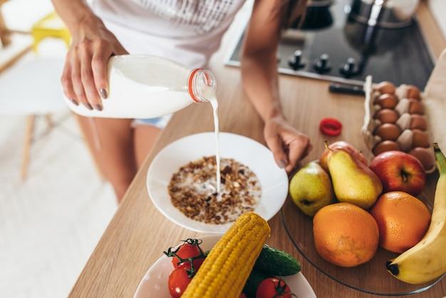 Woman pours milk into a bowl. muesli fruits vegetables.
