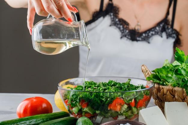Женщина наливает оливковое масло на салат в стеклянную емкость с помидорами, сыром, зеленью, огурцом, вид сбоку на серую поверхность