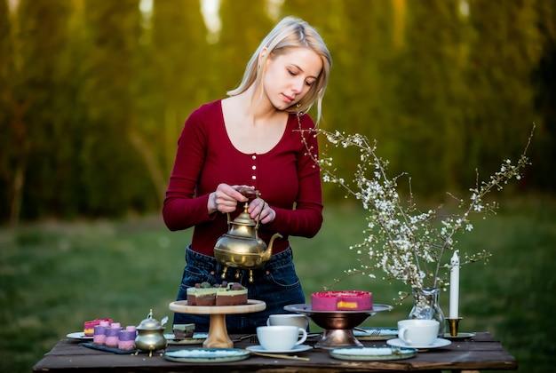 Женщина наливает чай во время чаепития в саду