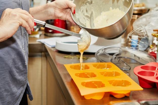 여자는 햇볕에 말린 토마토 머핀을 만들기 위해 반죽을 머핀 틀에 붓습니다.