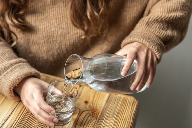 A woman pours water into a glass from a glass decanter