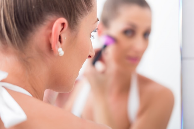Woman powdering her face with cosmetic brush