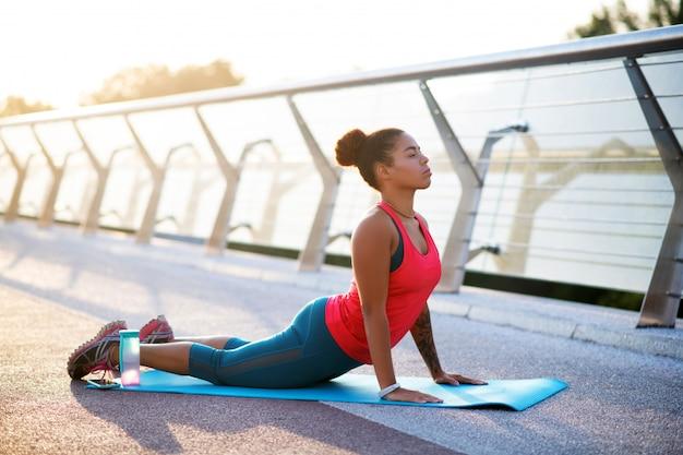 女性の練習。朝のヨガの練習を愛する浅黒い肌の若い女性