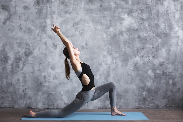 Практика женщины в фитнес-клубе. концепция йоги. стиль жизни.