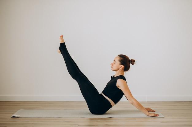 Женщина практикует пилатес в тренажерном зале йоги