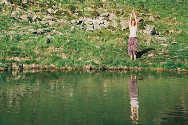 Женщина занимается йогой перед горным озером