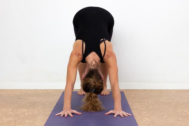 Woman practices adho mukha svanasana yoga pose over white background