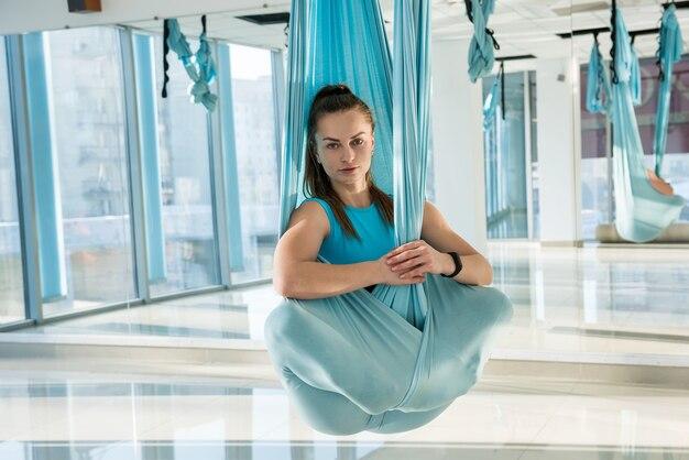 Женщина занимается воздушной йогой в гамаке. антигравитационный расслабляющий вид спорта. здоровье, концепция йоги летать.