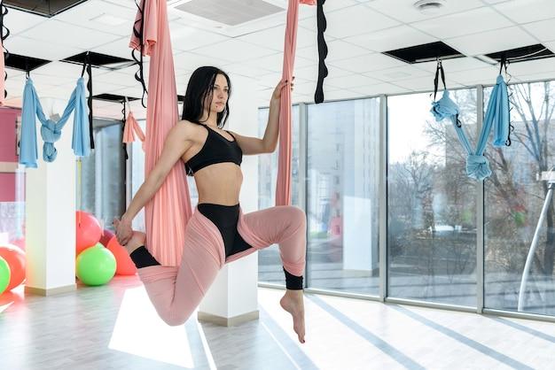 Женщина практикует антигравитационную йогу с гамаком в фитнес-студии. расслабляющие упражнения для здорового образа жизни